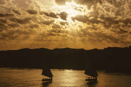 Cloudy sky with sunshine and traditional sailing boats called felucca sailing the Nile river. The largest watercourse on earth that crosses Egypt from south to north.