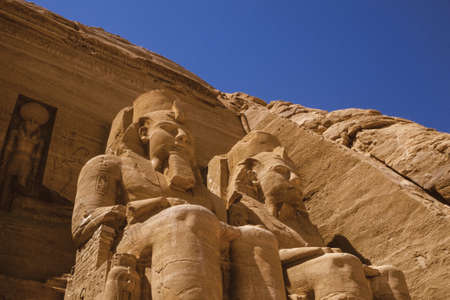 Colossal statues of pharaoh Ramses II carved into rock by the ancient Egyptians in the Abu Simbel Temple. An amazing archaeological complex on the lake shore of Aswan dam in southern Egypt.