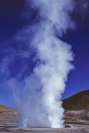 Water steam at the El Tatio geysers field in the Atacama desert highland. An extremely arid and mountainous region in northern Chile.