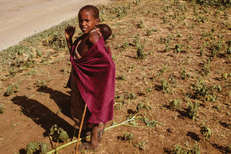 Serengeti, Tanzania - February 10, 1997. Inquisitive Maasai children dressed in typical clothes at Serengeti. A huge national park in the African savanna where several species of large mammals live.