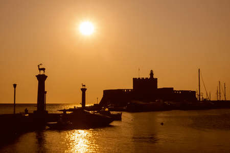 Silhouette of castle and sculptures at sunset in the entrance of Rhodes harbor. An ancient city with strong crusader influence on an island in the middle of the Aegean Sea, southern Greece.