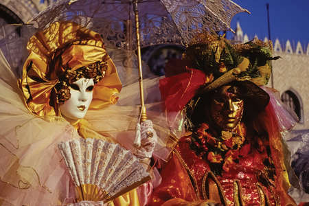 Carnival revelers wearing colorful and sophisticated costumes with masks in Piazza San Marco at the Carnival of Venice. The historic and amazing marine city full of canals and palaces in Italy.