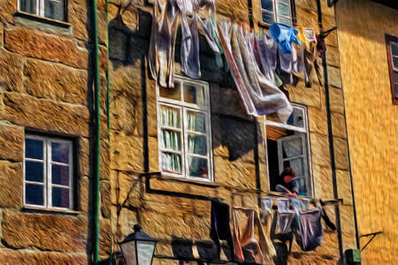Woman at the window of her house hanging clothes on the clothesline in Lisbon. An old city located along the Douro River estuary and the second-largest city in Portugal. Oil paint filter.