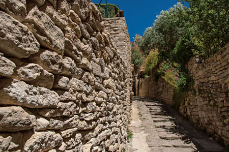 View of typical stone houses and wall with sunny blue sky, in alley of the historical city center of Gordes. Provence region, southeastern France. Фото со стока