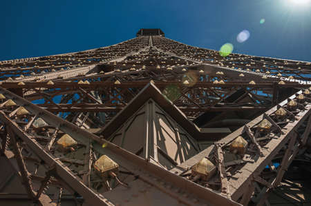 Perspective view of iron structure with sunlight at the Eiffel Tower in Paris. One of the most impressive world's cultural center. France. Фото со стока