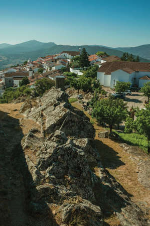 Old houses on top of ridge with trees and mountainous landscape, as seen from the Marvao Castle. An amazing medieval fortified village in Portugal. Фото со стока
