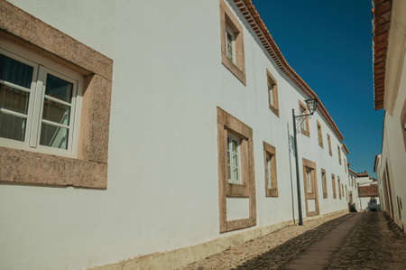 Facade of old whitewashed houses and cute windows in cobblestone alley, on a sunny day at Marvao. An amazing medieval fortified village in Portugal.