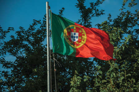 Close-up of Portuguese flag at sunset and tree branches on the background near Elvas. A gracious star-shaped fortress city in Portugal.