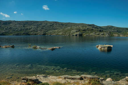 Fresh water at the Long Lake on highlands covered by bushes and rocks, at the Serra da Estrela. The highest mountain range in continental Portugal.