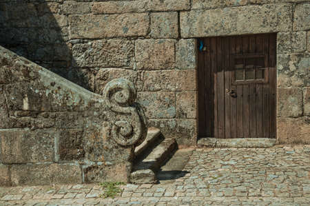 Stone staircase baluster with carved decoration, next to old gothic house with wooden door at Sortelha. A well preserved medieval village in Portugal.