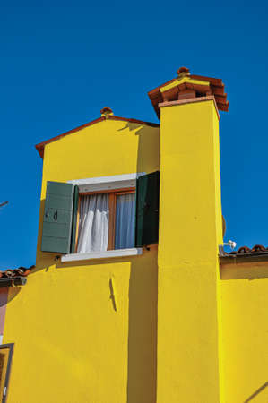 Chimney and window with open blinds in a colorful house on a sunny day in Burano, a gracious little town full of canals near Venice. Northern Italy.