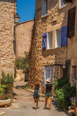 Chateaudouble, France - July 11, 2016. Woman and child walking in an alley with building and flowers in a sunny day at Chateaudouble, a village with medieval origin. Provence region, France.