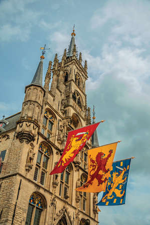 Richly decorated facade of Gothic City Hall and colorful flags in cloudy day at Gouda. A town popular for its typical cheese in Netherlands.