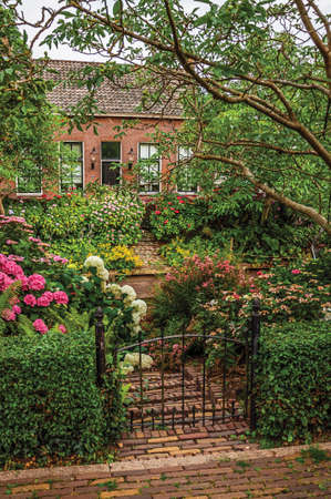 Charming rustic brick house with flowered garden, leafy trees and iron gate in a cloudy day at Drimmelen. A lovely small hamlet in Netherlands.