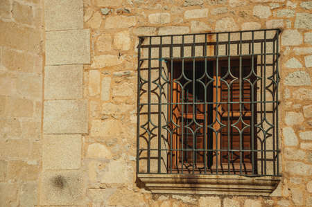 Wooden window with wrought iron grid on the stone facade of the gothic building, in a sunny day at Caceres. A fully preserved medieval town in Spain. 免版税图像