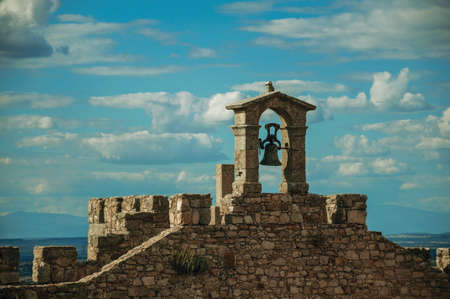 Bell on top of thick stone wall with crenels and merlons at the Castle of Trujillo. A small medieval town in Spain. 免版税图像