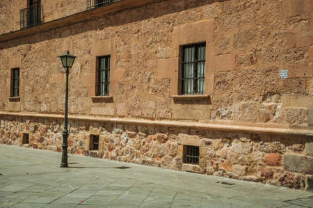 Deserted alley with old gothic building made of stone and public lamp at Salamanca. One of the most important university cities in Spain.