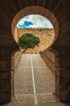 Gateway in typically Moorish style with a cobblestone ramp leading to the courtyard in the Castle of Trujillo. A small medieval town in Spain.