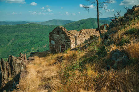 Ruined house on the cliff edge and green valley at the highlands of Serra da Estrela. The highest mountain range in continental Portugal.