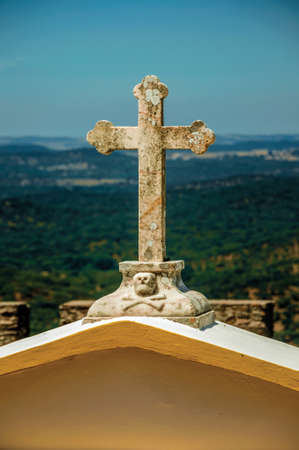 Close-up of marble cross on top of graveyard gateway in Evoramonte. A fortified civil parish over hill in Portugal. 免版税图像