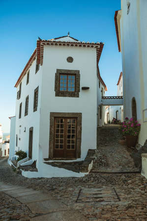 Facade of old corner house in between two cobblestone alleys on slope, in a sunny day at Marvao. An amazing medieval fortified village in Portugal. 免版税图像