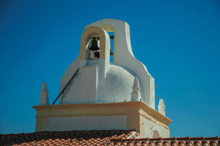 Close-up of bell on top of whitewashed dome over rooftop of an old house, in a sunny day at Marvao. An amazing medieval fortified village in Portugal.