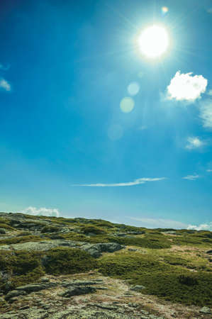 Hilly landscape in a sunny day covered by bushes and rocks on highlands of the Serra da Estrela. The highest mountain range in continental Portugal.
