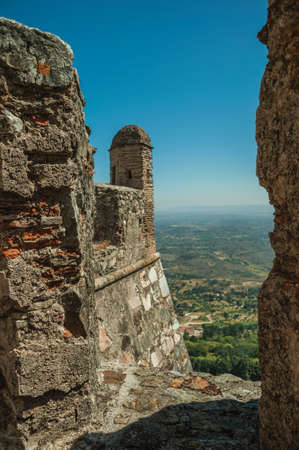 Stone wall and watchtower over cliff with hilly landscape seen by crenel in the Marvao Castle. An amazing medieval fortified village in Portugal.