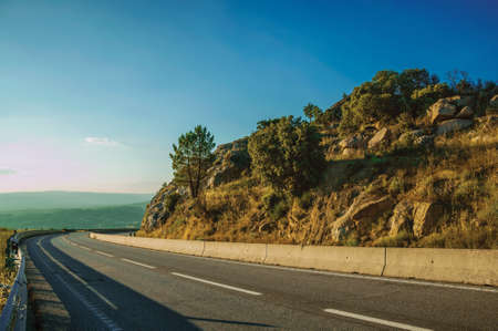 Country road passing on hilly landscape with rocks on sunset at the highlands of Serra da Estrela. The highest mountain range in continental Portugal. 免版税图像