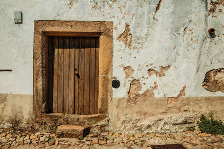 Old house with worn plaster wall and wooden door in cobblestone alley, on sunny day at Marvao. An amazing medieval fortified village in Portugal. 免版税图像