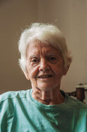 Portrait of old lady with white hair inside her house in Sao Paulo. The gigantic city, famous for its cultural and business vocation. Brazil.