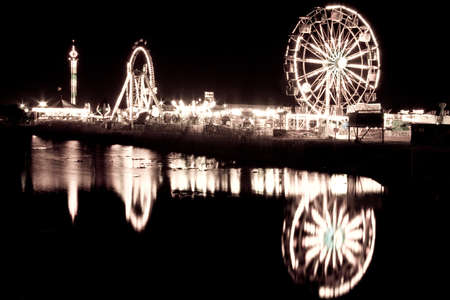 Night shot of a ferris wheel by the lake