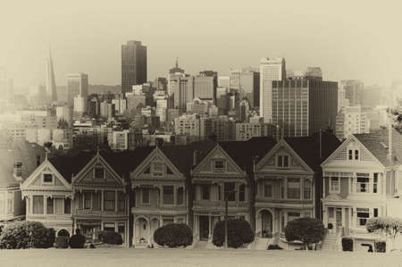 Victorian homes line on Steiner Street and the San Francisco skyline as seen from the Alamo Square Park