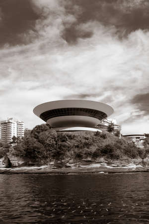 oscar: Contemporary Museum of Art in the city of Niteroi, Rio de Janeiro in Brazil. Round building by the water surrounded by vegetation.