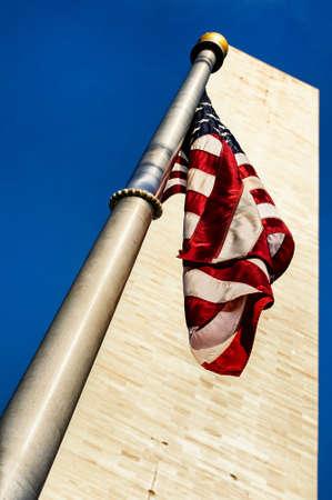 Low angle view of Washington Monument and American Flag, Washington DC, USA photo