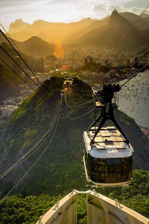シュガーローフ山、リオデジャネイロ、ブラジルに近づいている頭上式ケーブル車 写真素材