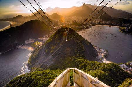 シュガーローフ マウンテン, リオ ・ デ ・ ジャネイロ、ブラジルに近づいている頭上式のケーブルカー 写真素材