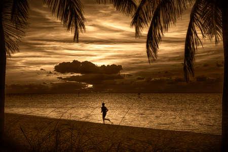 日没で、キー ウェスト モンロー郡、フロリダ州、アメリカ合衆国、ビーチを走る人のシルエット