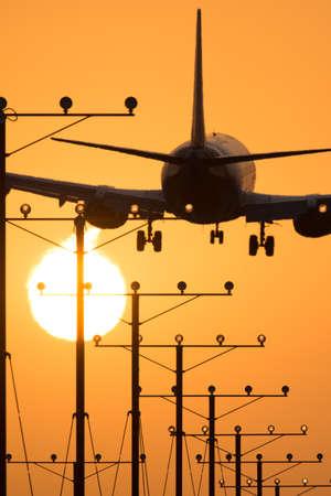 日没、ロスアンジェルス、カリフォルニア、米国の間にロサンゼルス国際空港に着陸する飛行機 写真素材