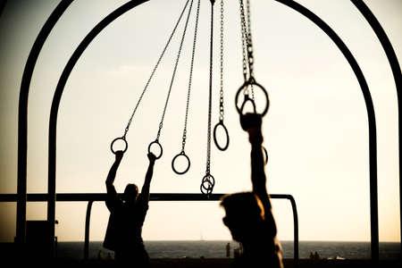 incidental people: Tourists swinging on rings on the beach, Santa Monica Beach, Santa Monica, Los Angeles County, California, USA