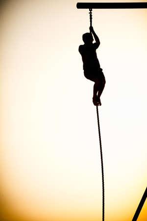 Silhouette of a person climbing a rope on the beach, Santa Monica Beach, Santa Monica, Los Angeles County, California, USA