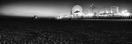 amusement park black and white: Ferris wheel on Santa Monica Pier lit up at dusk, Santa Monica, Los Angeles County, California, USA Stock Photo