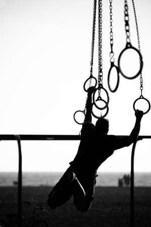 サンタ モニカー ビーチ、サンタモニカー、ロサンゼルス郡、カリフォルニア州、ビーチでリング上を振る人のシルエット 写真素材
