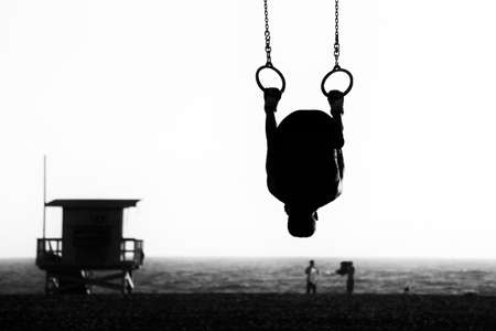 Silhouette of a person swinging on rings on the beach, Santa Monica Beach, Santa Monica, Los Angeles County, California, USA photo