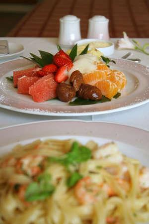Close-up of fruit salad dessert with big shrimp pasta Standard-Bild