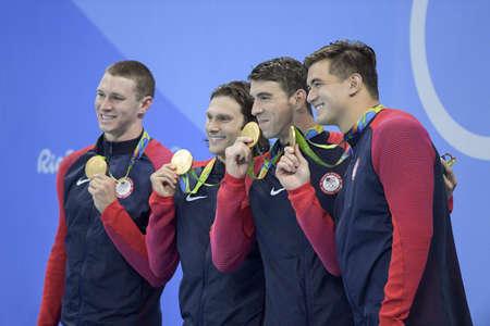 Rio de Janeiro, Brazilië - 13 augustus 2016: Michael Phelps, Ryan Murphy, Cody Miller en Nathan Adrian (USA) tijdens de 4x100m wisselslag estafettefinal van de Olympische spelen in Rio 2016 vieren de overwinning