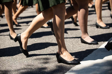 Women military marching in a street. Legs and shoes in line.