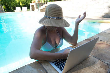 middle-aged woman working on the laptop inside the pool on very hot summer day