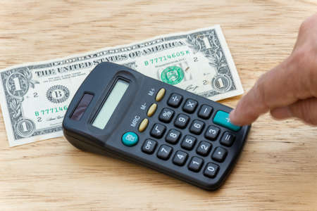 person making account, in a pocket calculator with a wooden background. Finger in motion