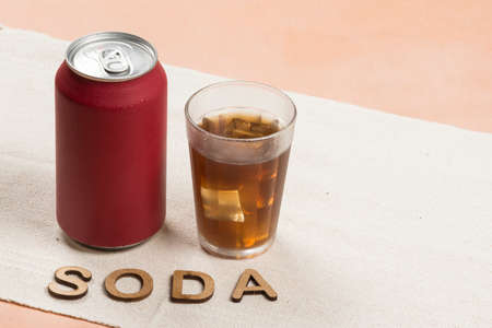 red soda can with a glass filled with ice. Word Soda